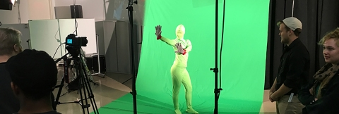 A student performing in front of a green screen