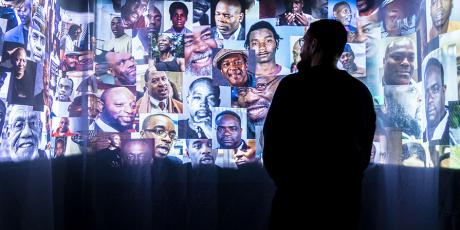 A viewer stands in front of a multi-media art installation